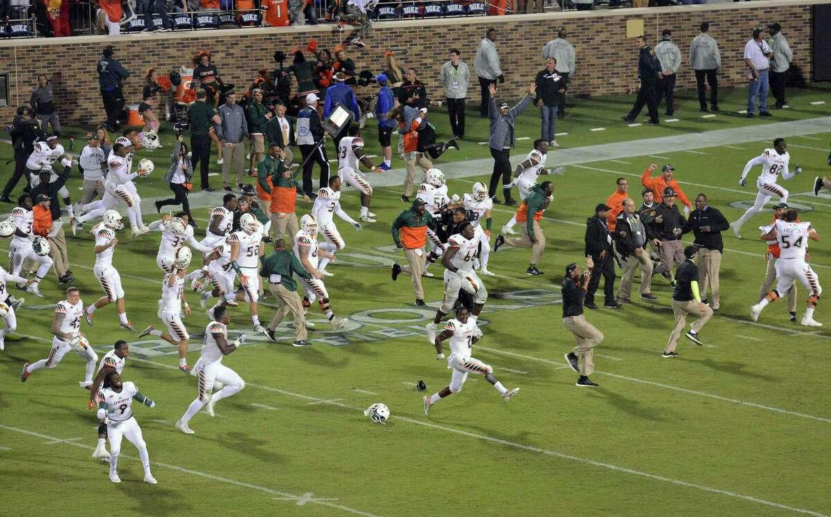 Miami players run onto the field to celebrate their 30-27 win over Duke Saturday.