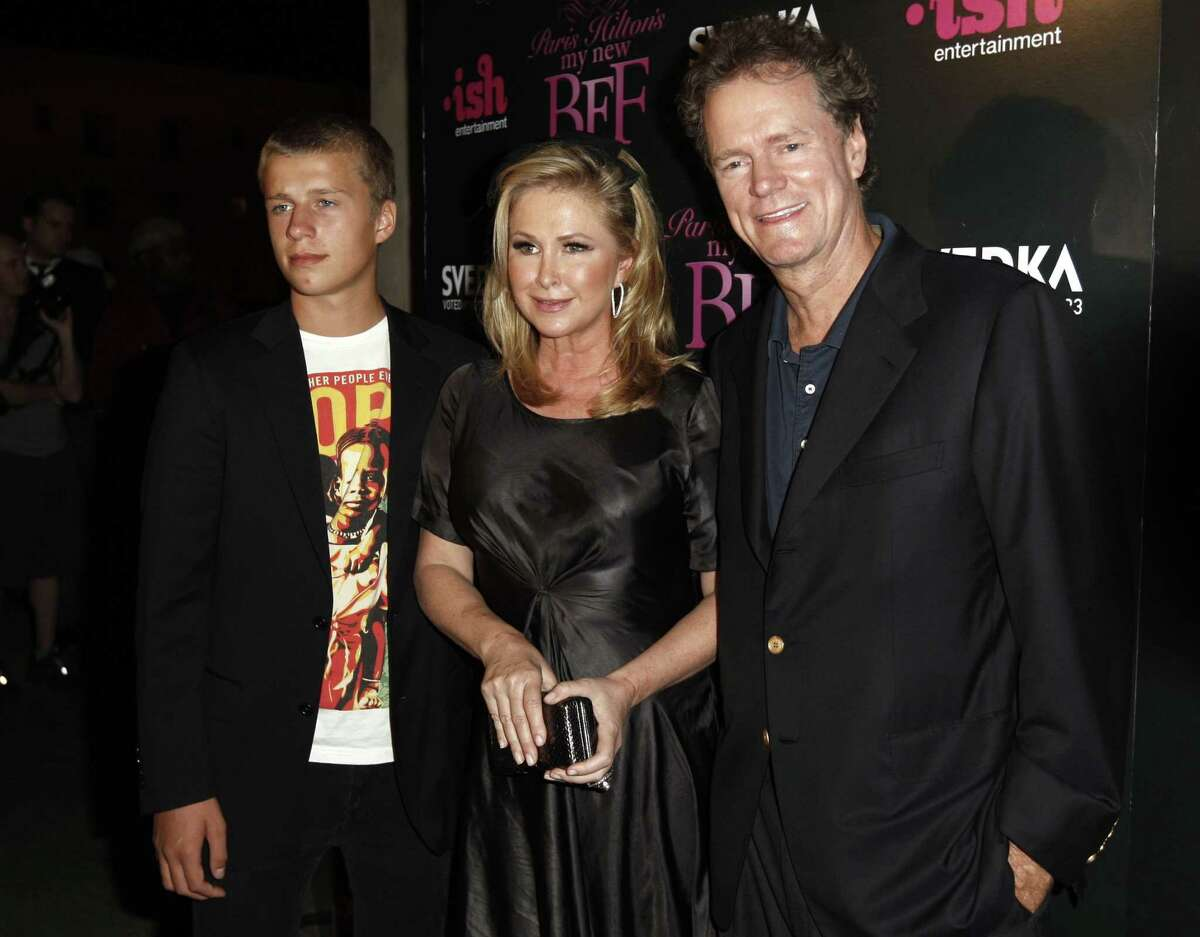 """FILE - In this Sept. 30, 2008, file photo, Conrad Hilton, left, Kathy Hilton, center, and Rick Hilton arrive at the launch party of new MTV series """"Paris Hilton's My New BFF"""" in Los Angeles. Federal prosecutors in Los Angeles say Paris Hilton's brother Conrad has agreed to plead guilty to assaulting flight attendants on a trip from London last year. The U.S. attorney's office says Hilton signed the agreement Tuesday, March 3, 2015. He's set to appear in court Thursday but will officially plead guilty to the misdemeanor later. (AP Photo/Matt Sayles, File)"""