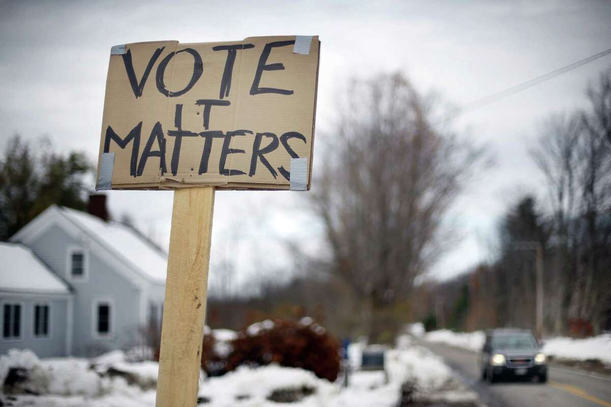 A handmade sign stuck in a snowbank on a rural road urges citizens to vote, Tuesday, Nov. 4, 2014, in Searsmont, Maine. (AP Photo/Robert F. Bukaty)