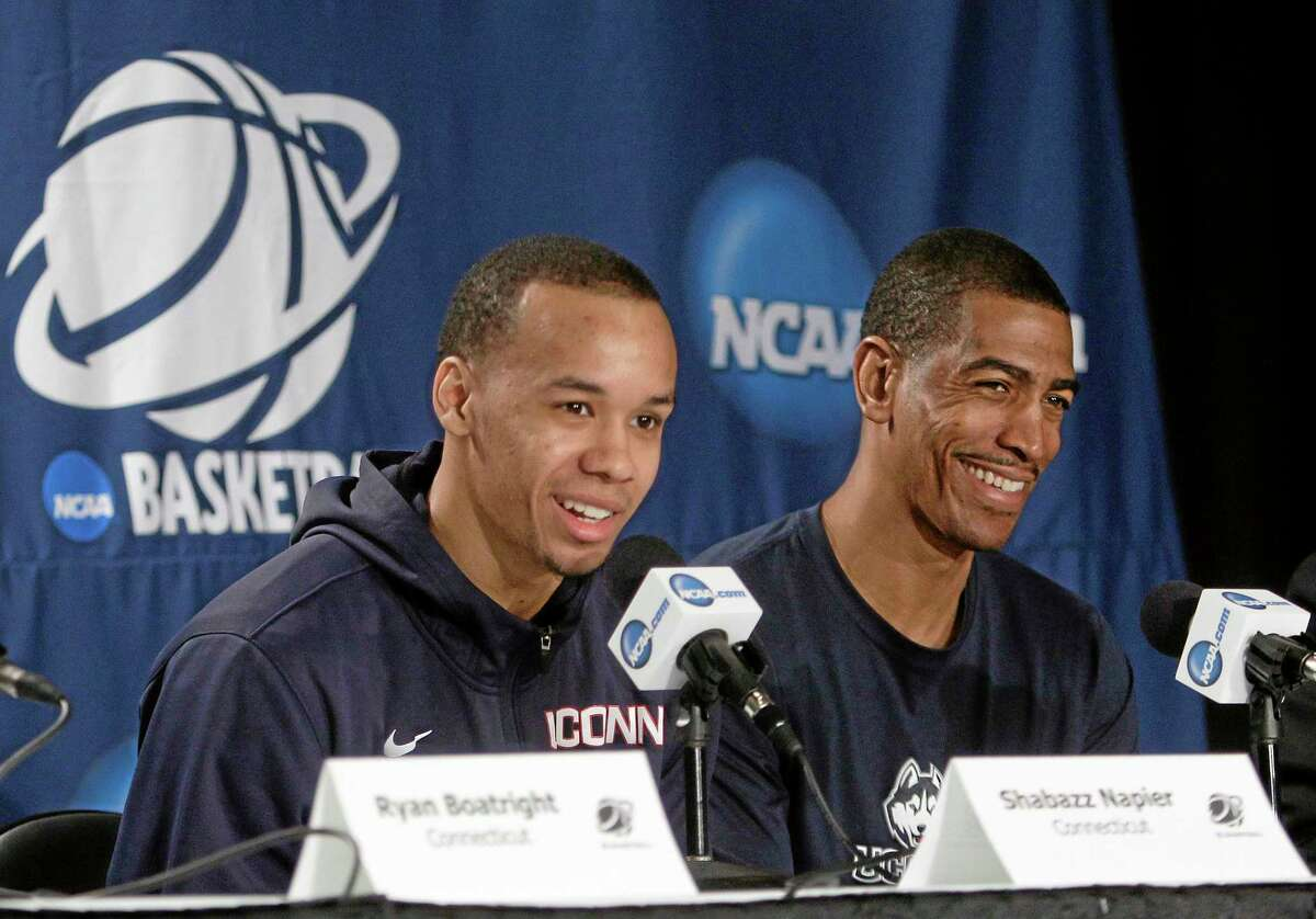 UConn head coach Kevin Ollie, right, reacts as Shabazz Napier responds to a question during a news conference Saturday in New York.