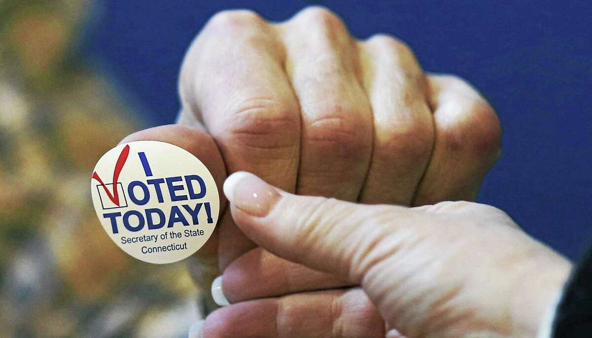 """In this Nov. 6, 2012, file photo, poll worker Chris Theriot hands out an """"I Voted Today!"""" sticker after a resident placed her ballot in the box at the North Street School in Greenwich."""