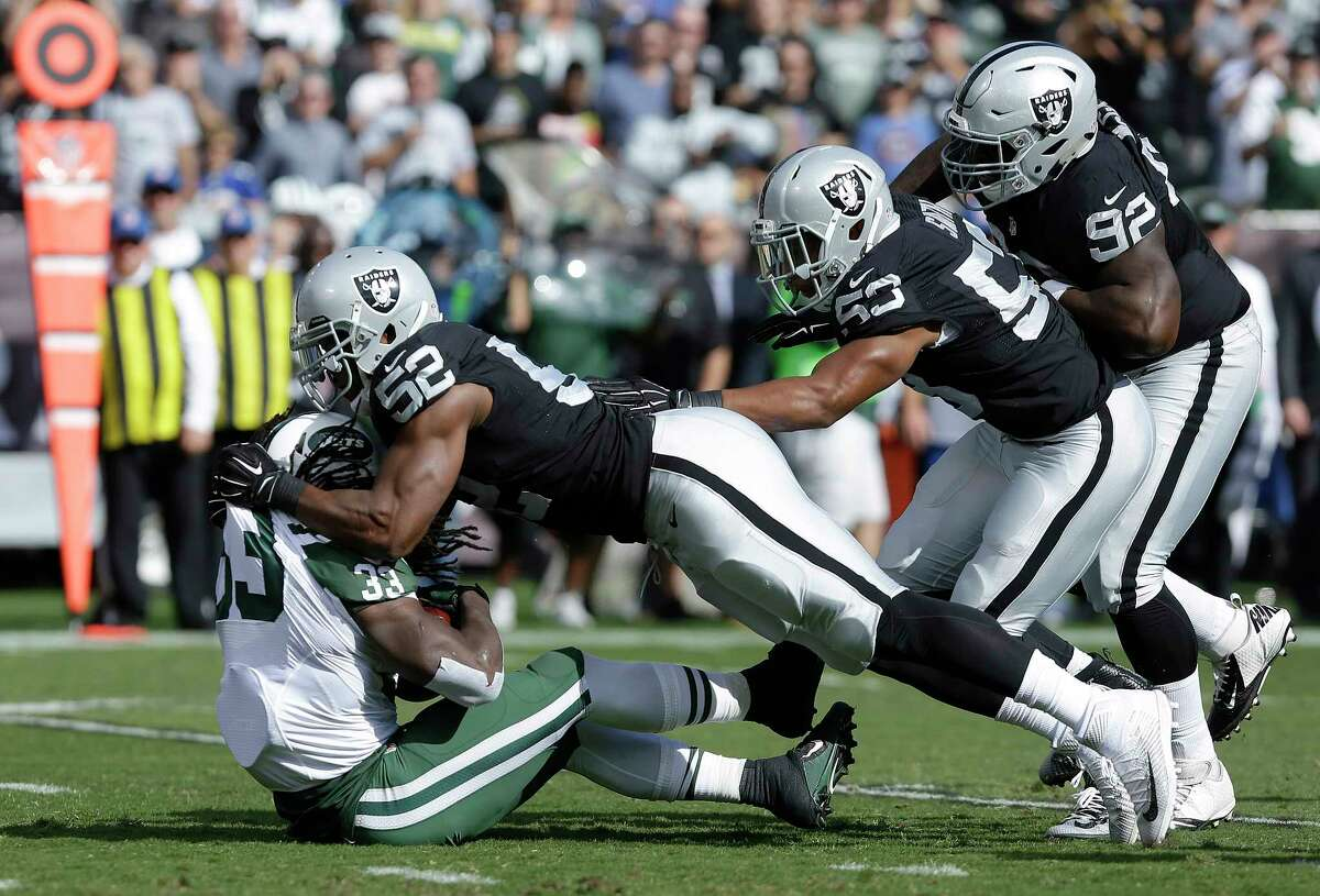Raiders outside linebacker Khalil Mack (52) tackles Jets running back Chris Ivory during the first half Sunday.