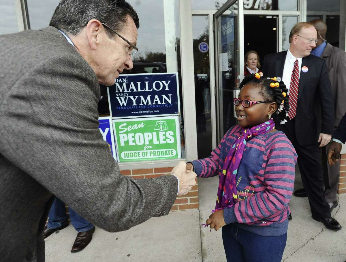 Connecticut Gov. Dannel P. Malloy greets Krista Bamfo, 7, of Manchester, outside Manchester Democratic headquarters on Election Day, Tuesday, Nov. 4, 2014, in Manchester, Conn. Malloy is facing Republican candidate Tom Foley. (AP Photo/Jessica Hill)