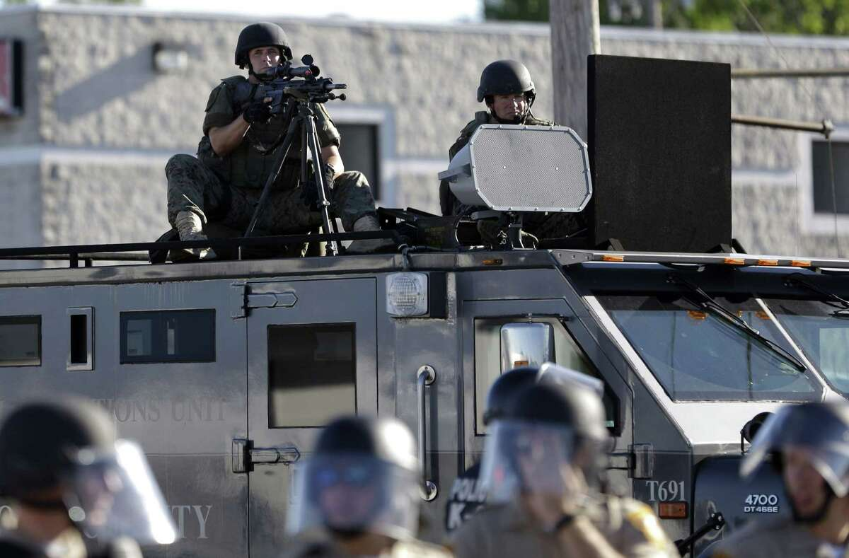 In this Aug. 9, 2014, file photo, a police tactical team moves in to disperse a group of protesters in Ferguson, Mo. that was sparked after Michael Brown, an unarmed black 18-year-old, was shot and killed by white police officer Darren Wilson. A Justice Department investigation has found patterns of racial bias in the Ferguson police department and at the municipal jail and court.