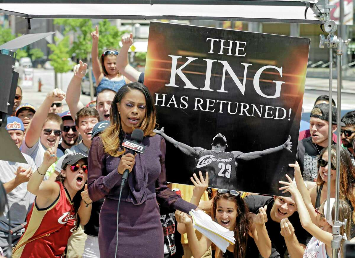 Fans whoop it up behind an ESPN reporter outside Quicken Loans Arena in Cleveland after LeBron James announced he would return to the Cavaliers on Friday.