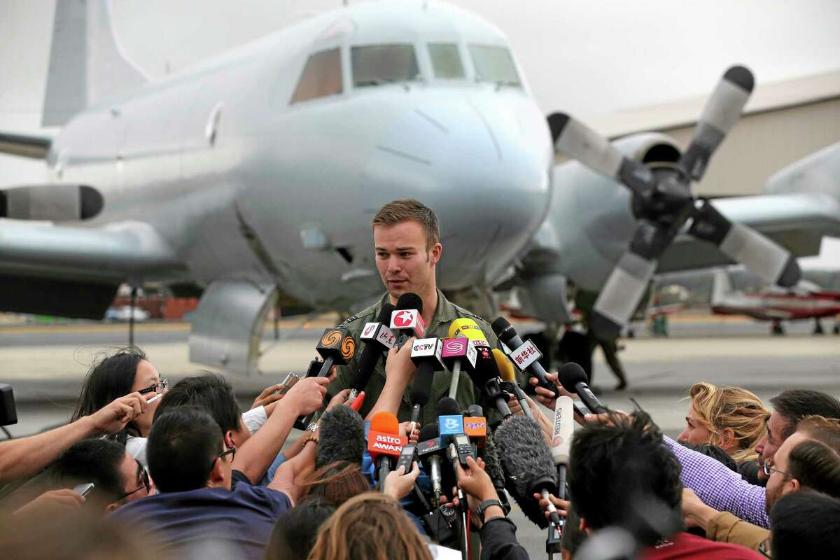 Royal Australian Air Force (RAAF) pilot Flight Lt. Russell Adams speaks to the media his AP-3C Orion returned from searching for debris or wreckage of the missing Malaysia Airlines Flight MH370 in Perth, Australia, Saturday, March 29, 2014. Russell reported they were did not see or locate and wreckage searching in reasonably good wether with a vision of four or five kilometers but the sea state was up causing some whites caps making it difficult for the visual spotters.(AP Photo/Rob Griffith, Pool)