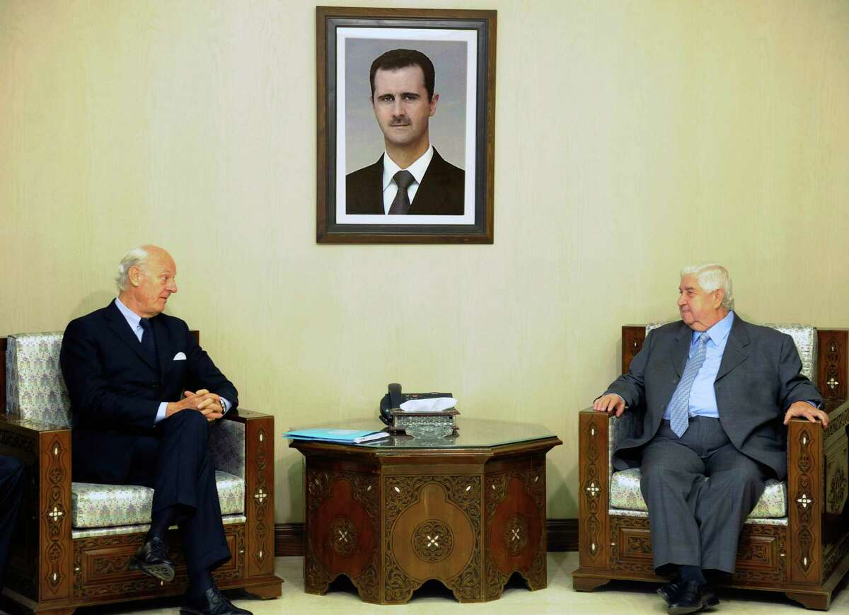 In this photo released by the Syrian official news agency SANA, Syria's Foreign Minister Walid al-Moallem, right, meets with U.N. Special Envoy for Syria Staffan de Mistura in Damascus, Syria on Nov. 1, 2015.