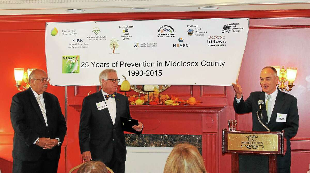 MCSAAC President Tony Salvatore, left, and Chamber of Commerce Prevention Committee Chairman Harry Burr, center, look on as Gary Vallo, president of MiddleOak, accepts The Harry Eben Burr Business Award at the 25th annual meeting of the Middlesex County Substance Abuse Action Council Oct. 23.