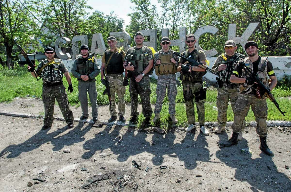 Ukrainian government troops pose for a photo in front of a sign that reads 'Slovyansk', after heavy fighting between pro-Russian fighters and Ukrainian government troops just outside Slovyansk, eastern Ukraine, Thursday, July 10, 2014. In the past two weeks, Ukrainian government troops have halved the amount of territory held by the rebels. Now they are vowing a blockade of Donetsk. In another sign of deteriorating morale among rebels, several dozen militia fighters in Donetsk abandoned their weapons and fatigues Thursday, telling their superiors they were returning home. (AP Photo/Evgeniy Maloletka)