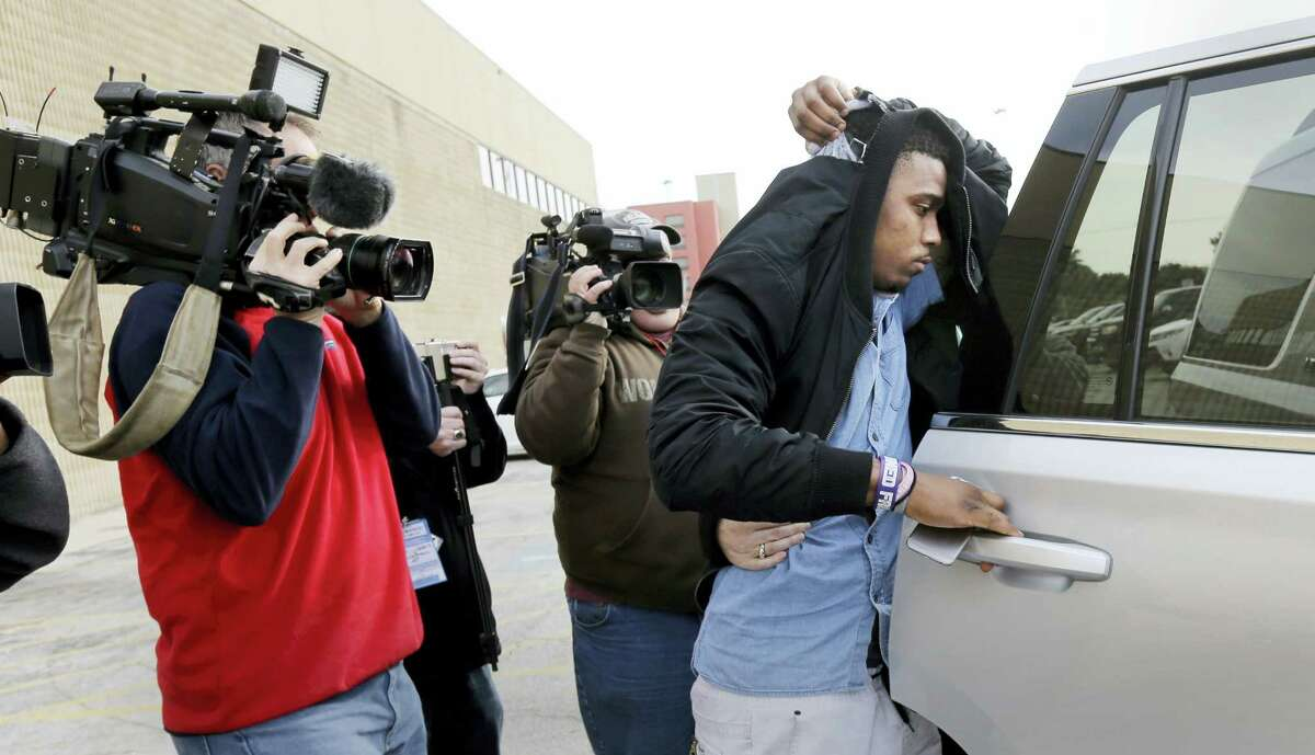 TCU quarterback Trevone Boykin, right, holds a jacket over his head as he is escorted from a detention center after he was released on bail Thursday in San Antonio.