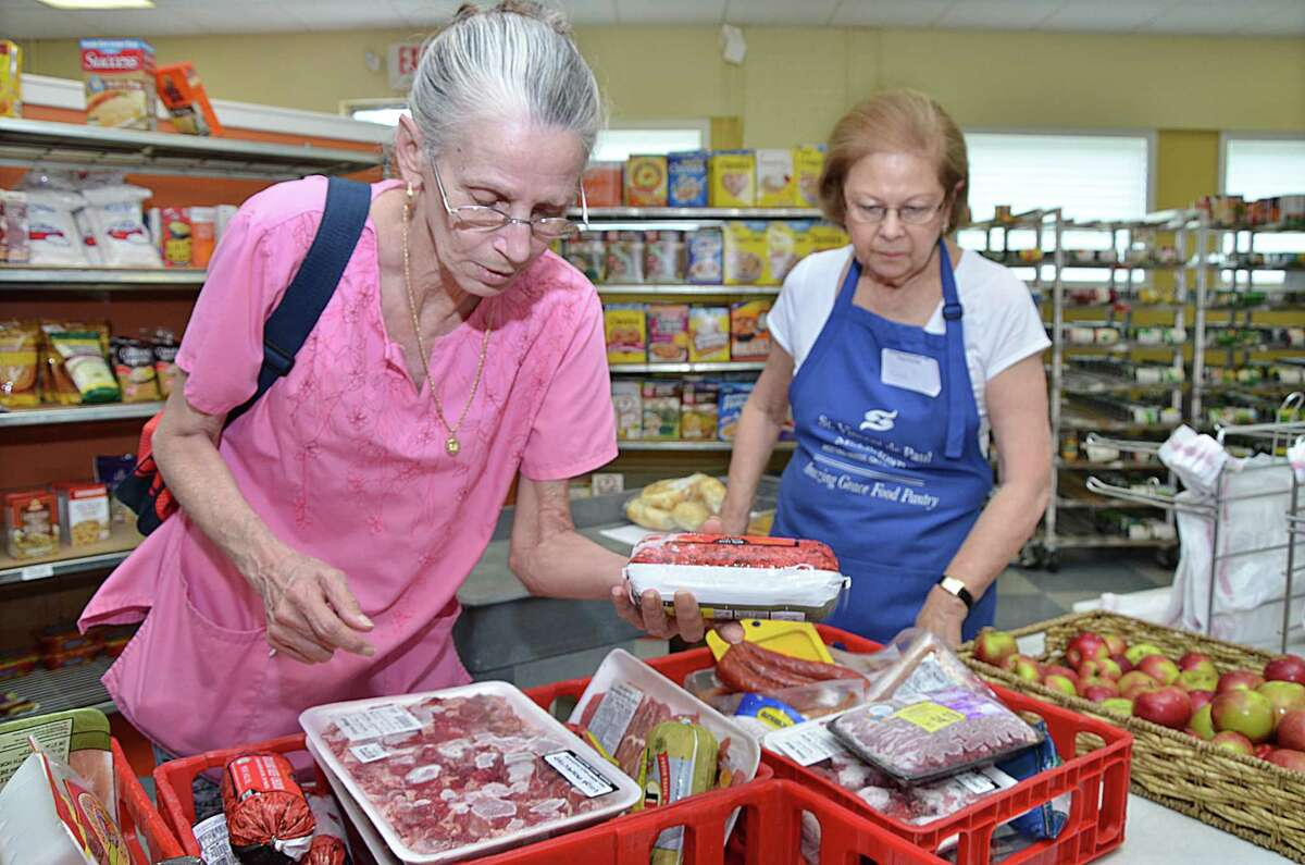 """Catherine Avalone - The Middletown Press Middletown resident Marcia Wrubel, at right, a volunteer at Amazing Grace Food Pantry helps Deborah Cyr, of Middletown shop for her groceries Friday afternoon. Food donations are accepted at 16 Stack Street in Middletown on Mondays, Wednesdays and Fridays from 10am to 5pm and on Saturdays from 9am to 1pm. Wrubel said, """"I'm here because I love it. This is the best thing I've ever done. We are serving 1,000 a month."""" """"It think it an awesome thing, if it weren't for Amazing Grace, a lot of people would not be eating."""""""