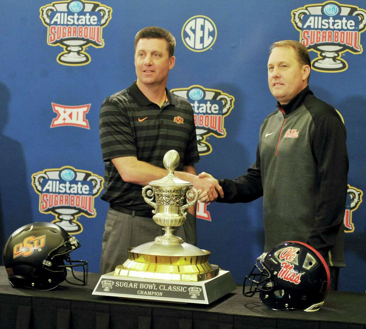 Oklahoma State head coach Mike Gundy, left, and Mississippi head coach Hugh Freeze pose with the trophy during a press conference for the Sugar Bowl Thursday in New Orleans.
