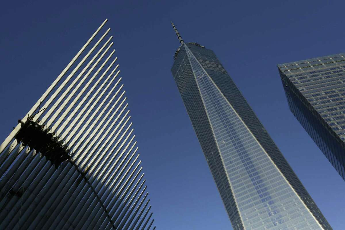 One World Trade Center, center, stands between the transportation hub, left, still under construction, and 7 World Trade Center, second from right on Nov. 3, 2014 in New York.