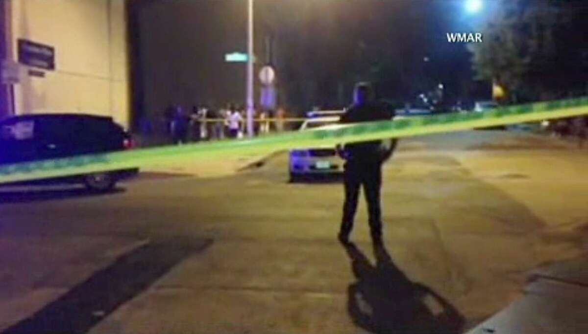 In this image taken from video, police investigate the scene of a shooting on July 7, 2015 in Baltimore. Baltimore police say four people have been shot, three fatally, near the University of Maryland, Baltimore, campus.