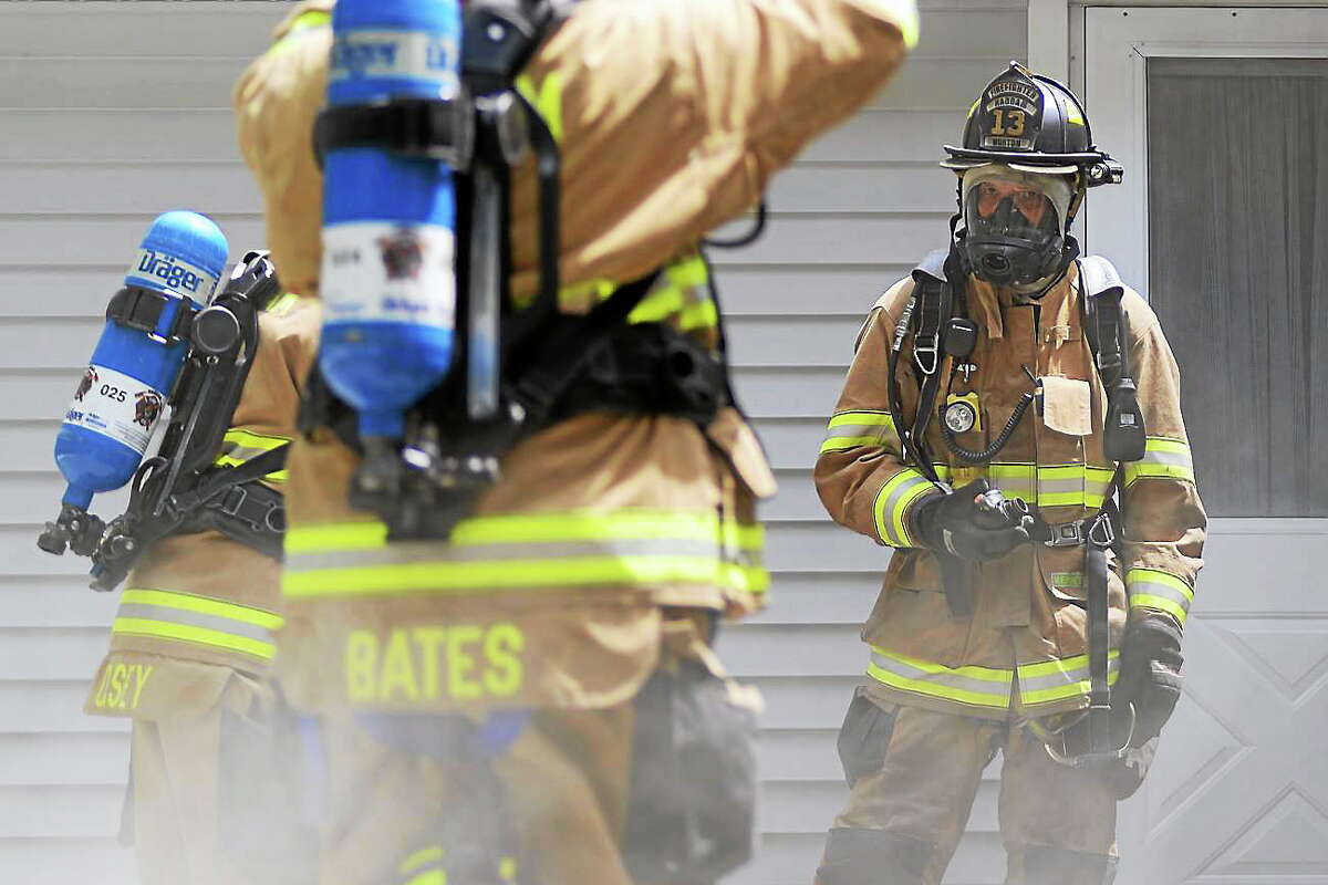 Haddam Firefighter Robert Norton Jr. stands outside a residence on Park Road on June 29. Light smoke conditions were reported in the vacant home.