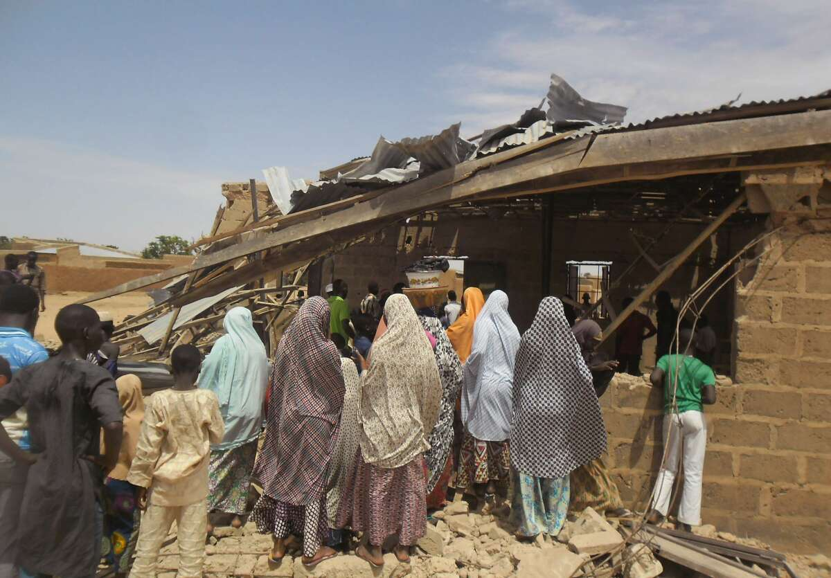 People gather around the Redeemed Christian Church of God, after a bomb blast in Potiskum, Nigeria on July 5, 2015. A woman suicide bomber blew up in the midst of a crowded evangelical Christian church service in northeast Nigeria on Sunday and killed at least five people, witnesses said.