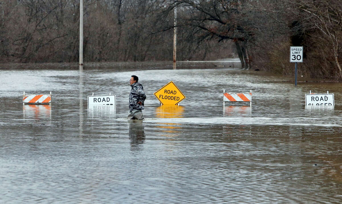 A man crosses Smizer Mill Road in southwest St. Louis County Wednesday.