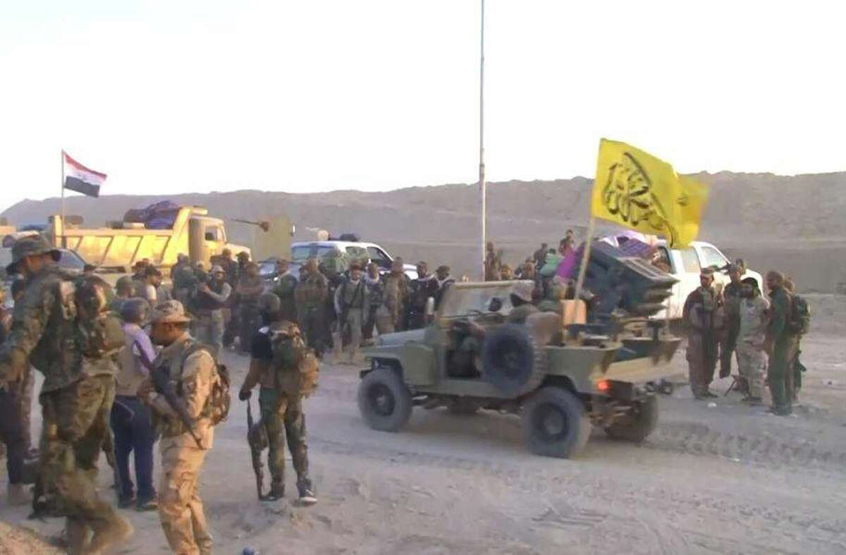In this July 5, 2015 photo, Iraqi security forces and allied Shiite militiamen stage outside the city of Fallujah, 40 miles (65 kilometers) west of Baghdad, Iraq as they prepare to attack Islamic State group positions.