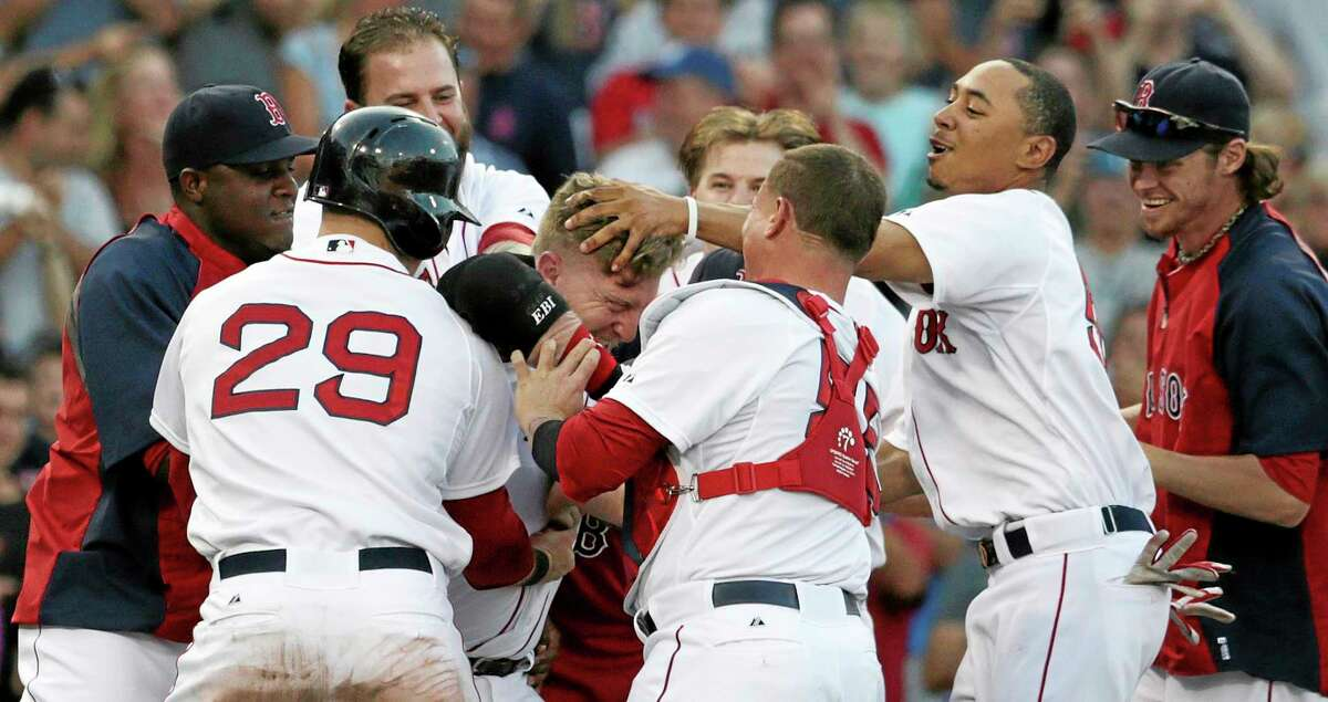 Red Sox pinch hitter Mike Carp, center is congratulated by teammates after his walk-off RBI single Thursday against the White Sox.