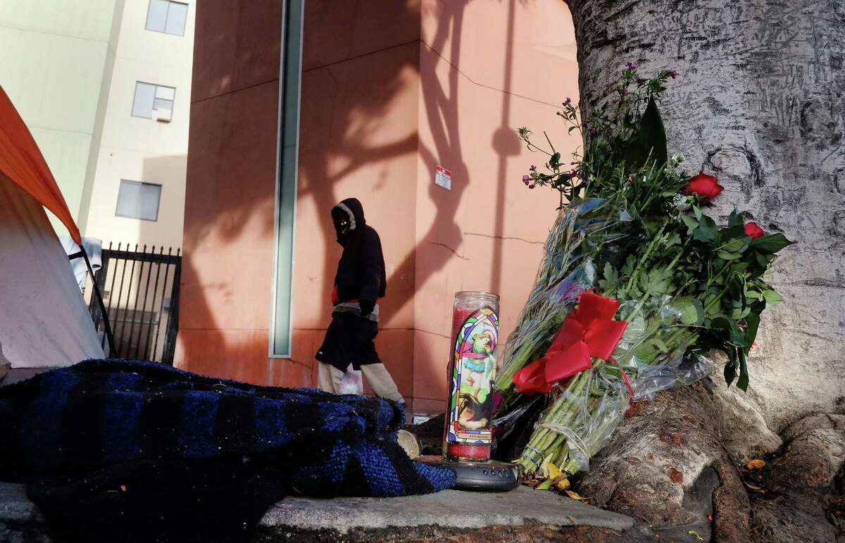 A pedestrian walks past flowers and candles, Monday, March 2, 2015, placed on a sidewalk near where a man was shot and killed Sunday by police in the Skid Row section of downtown Los Angeles. Three Los Angeles police officers shot and killed the man as they wrestled with him on the ground, a confrontation captured on video that millions have viewed online. Authorities say the man was shot after grabbing for an officer's gun. (AP Photo/Richard Vogel)