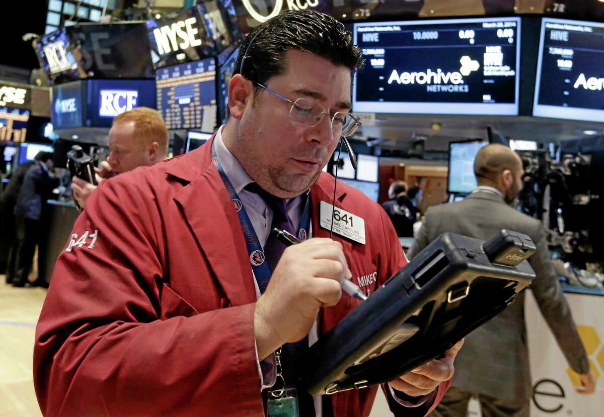 Trader Michael Capolino, center, works on the floor of the New York Stock Exchange Friday.