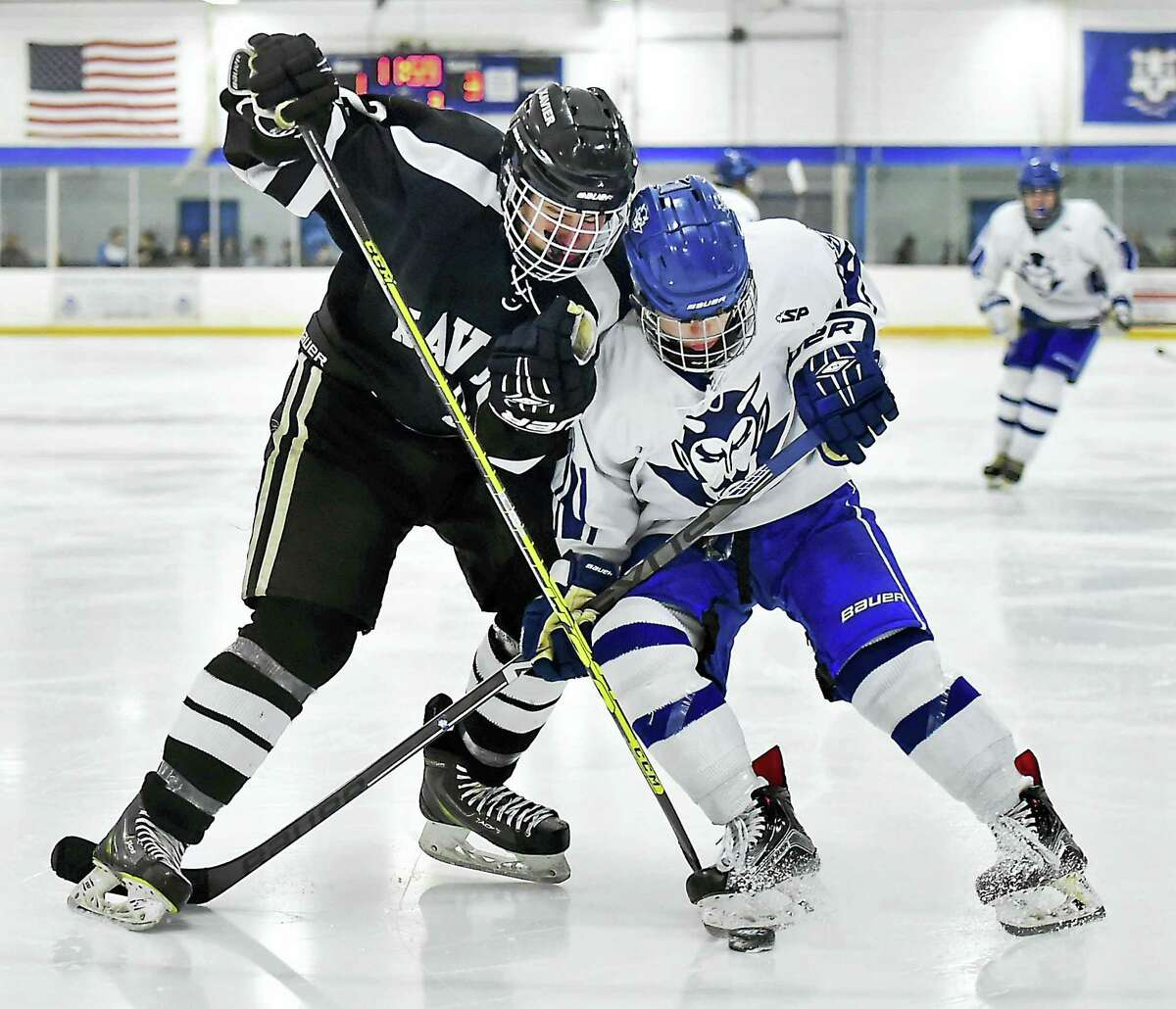 Xavier's Ryan Child (2) battles West Haven's Peter Richetelli for the possession Wednesday at the West Haven High School Christmas Tournament at the Edward L. Bennett Rink. Xavier won, 5-2.