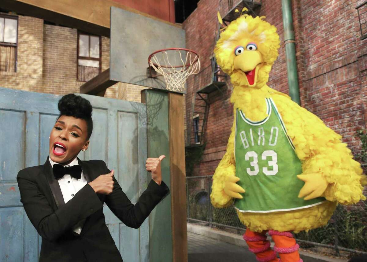"""In this Dec. 9, 2013 image released by the Sesame Workshop, singer Janelle Monae, left, and character Big Bird appear in a scene from the """"Power of Yet"""" sketch at Kaufman-Astoria Studios in the Astoria neighborhood of the Queens borough of New York."""