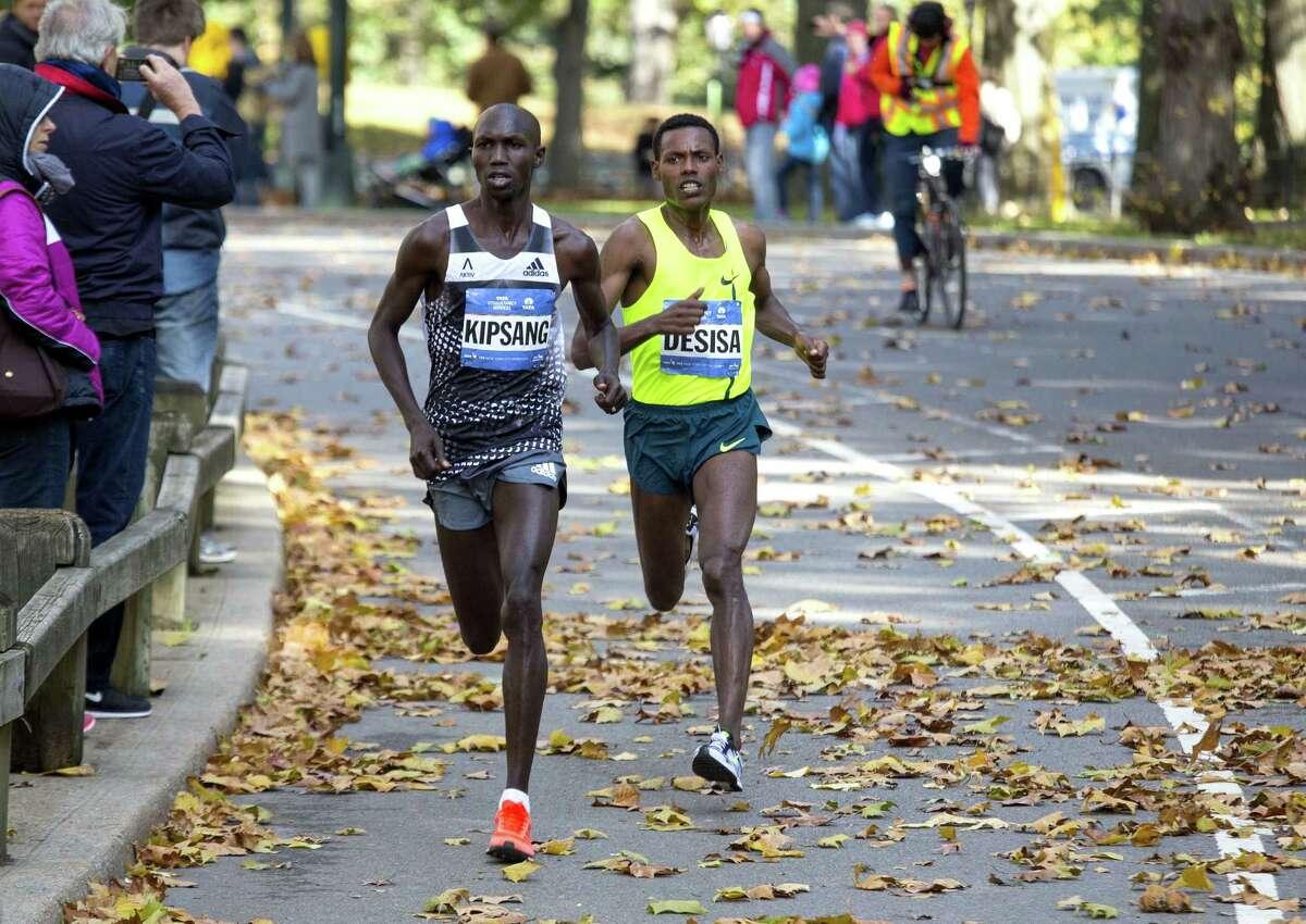 Wilson Kipsang, of Kenya, battles Lelisa Desisa, of Ethiopia, in Central Park during the final moments of the New York City Marathon Sunday.