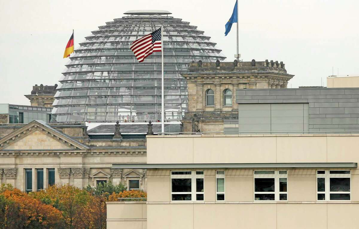 """FILE - in this Oct. 25, 2013 file photo the American flag flies on top of the U.S. embassy in front of the Reichstag building that houses the German Parliament, Bundestag, in Berlin, Germany. Germany took the dramatic step Thursday of asking the top U.S. intelligence official in Berlin to leave the country, following two reported cases of suspected U.S. spying and the yearlong spat over eavesdropping by the National Security Agency. """"The representative of the U.S. intelligence services at the United States embassy has been asked to leave Germany,"""" government spokesman Steffen Seibert said in a statement, Thursday, July 10,2014. (AP Photo/Michael Sohn, File)"""
