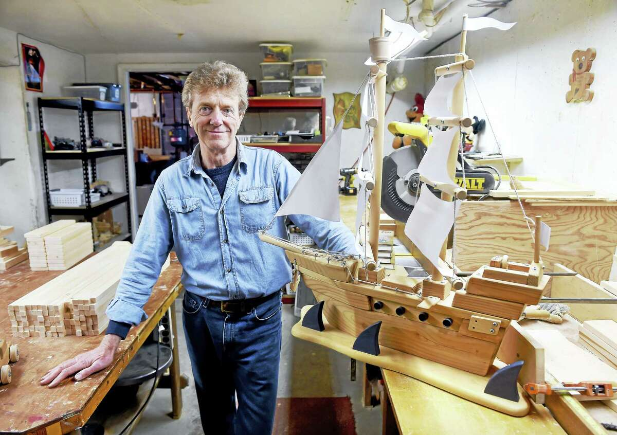 """Robert """"Woody"""" Wilkins, founder of Dances With Wood, is photographed at home in Clinton with a completed pirate ship made from a kit."""