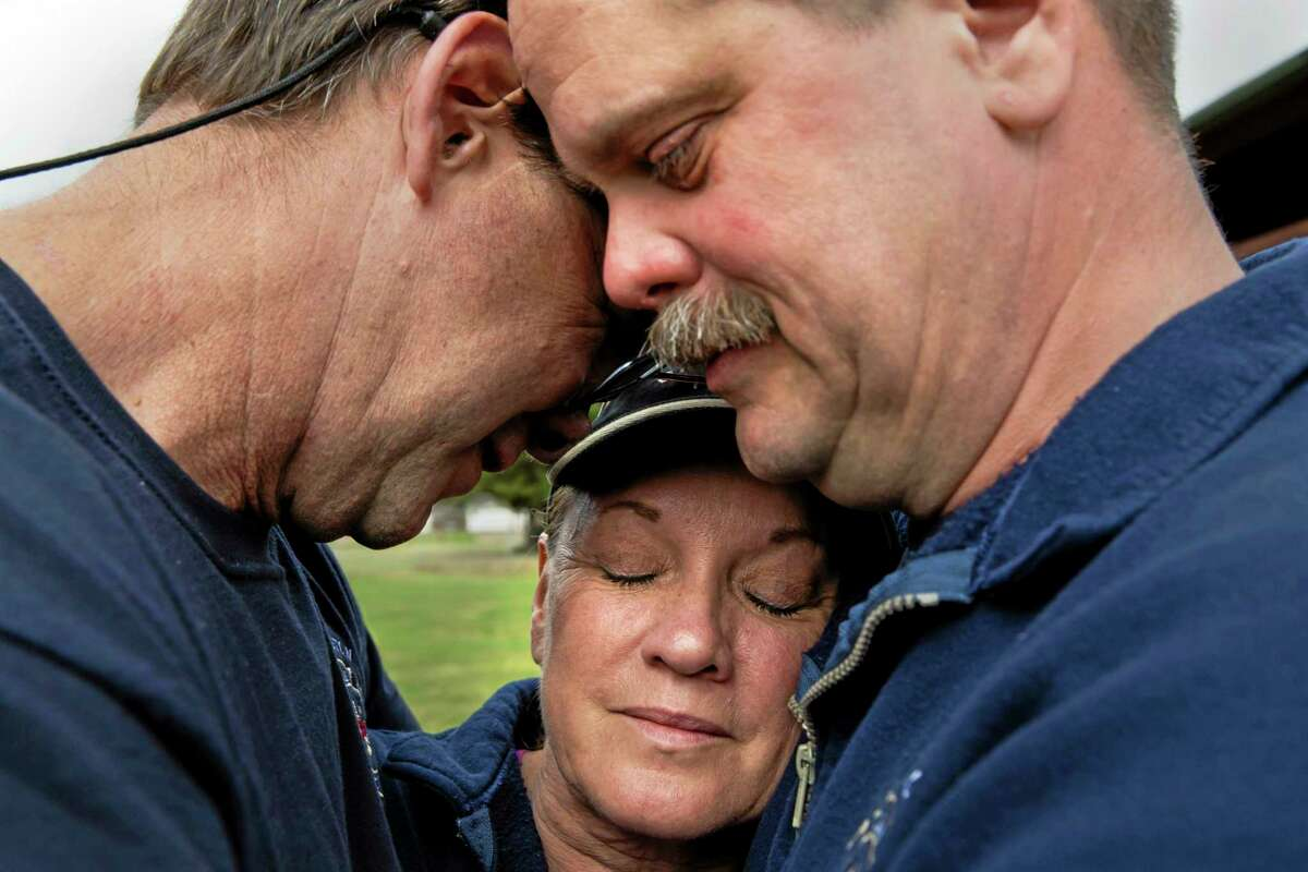 Darrington Fire District 24 volunteer firefighters, Jeff McClelland , from left, Jan McClelland and Eric Finzimer, embrace each other after saying a prayer for the victims and survivors of the massive mudslide above the North Fork of the Stillaguamish River onto Highway 530, in Darrington, on Wednesday, March 26, 2014. (AP Photo/The Seattle Times, Marcus Yam)