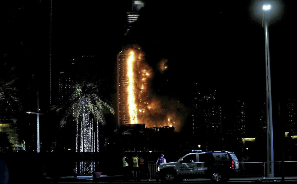 Smoke and flames pouring from a residential building, which also contains the Address Downtown Hotel, in Dubai, United Arab Emirates, Thursday evening, Dec. 31, 2015.