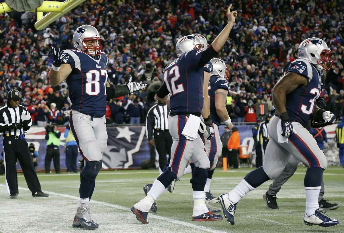 Patriots tight end Rob Gronkowski, left, reacts after catching a touchdown pass from quarterback Tom Brady, celebrating at center, in the second half Sunday.