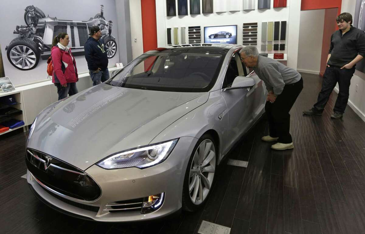 In this March 17, 2014, photo, Tesla representative John Van Cleave, right, shows customers Sarah and Robert Reynolds, left, and Vince Giardina, a new Tesla Model S all-electric car, at a Tesla showroom inside the Kenwood Towne Centre in Cincinnati.