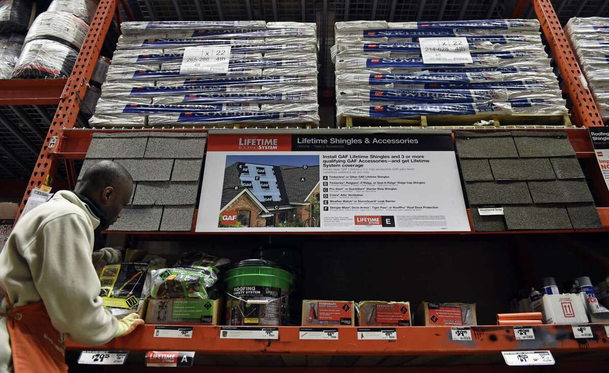 In this Feb. 23, 2015 photo, Prince Addy of Manassas, Va., straightens up the shelves of roofing products at the Home Depot in Falls Church, Va. A harsh winter has taken a toll on many roofs around the country. The first step in roof maintenance may be to get out a pair of binoculars and take stock.