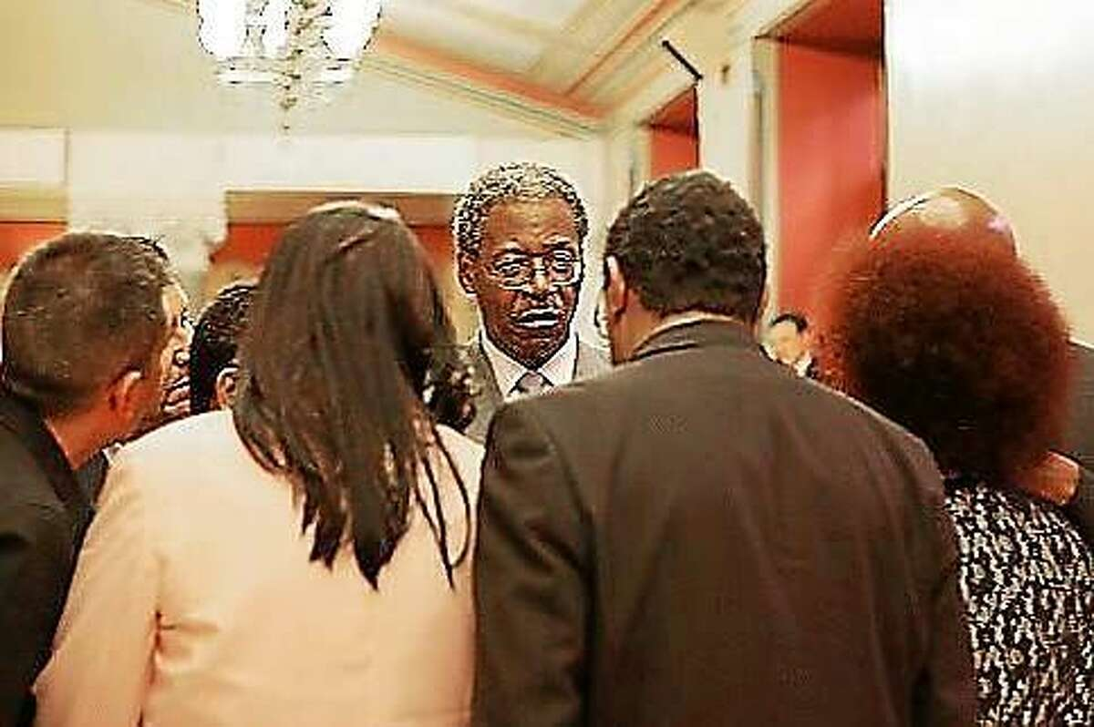 Sen. Eric Coleman, D-Bloomfield, talks strategy before a filibuster by the Black and Puerto Rican Caucus on the last day of the legislature's regular session.
