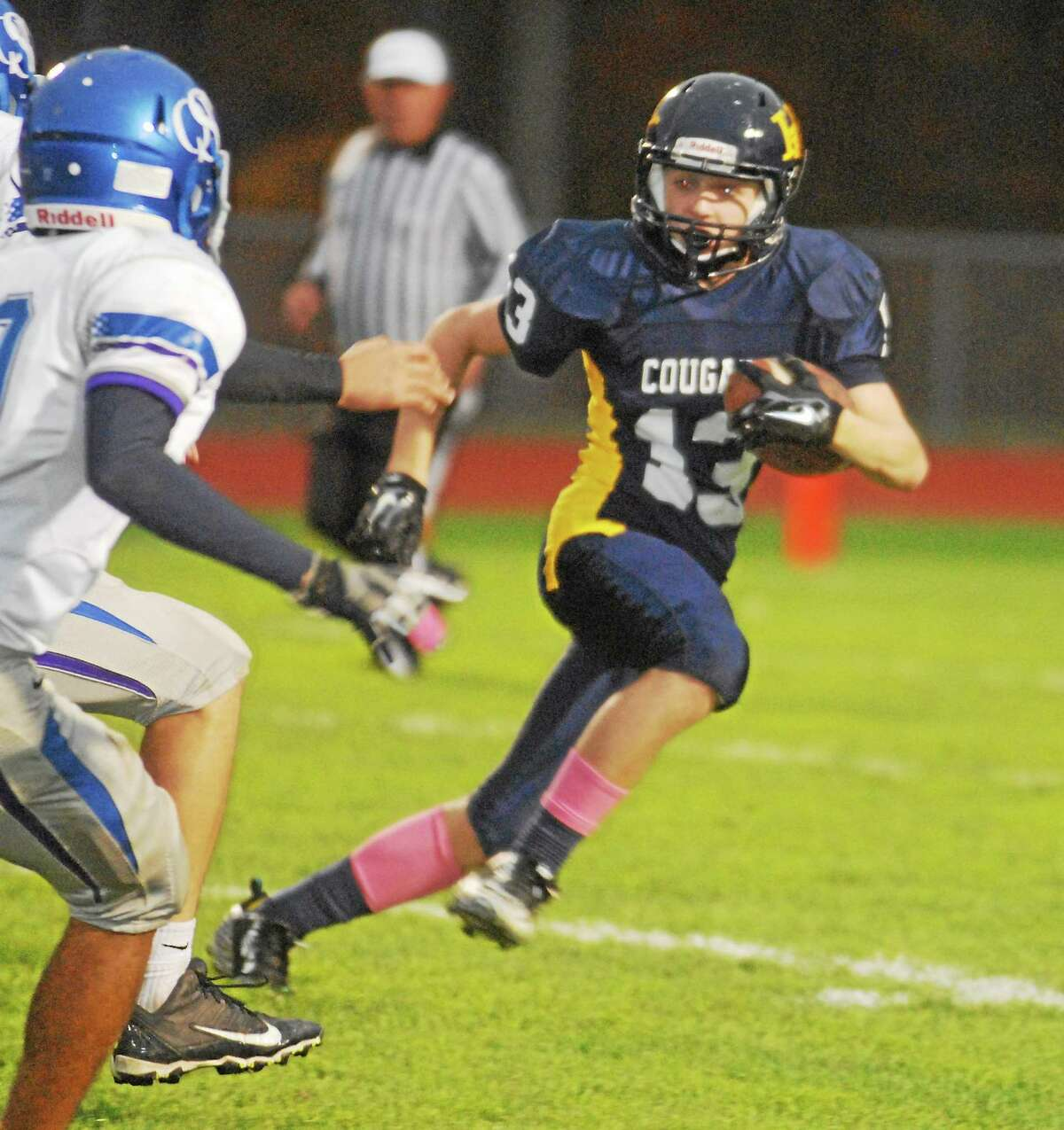 Haddam-Killingworth junior receiver Nate DeRita tries to elude Old Saybrook-Westbrook defenders Friday night. DeRita had seven receptions and two touchdowns in the Cougars' 43-13 win.