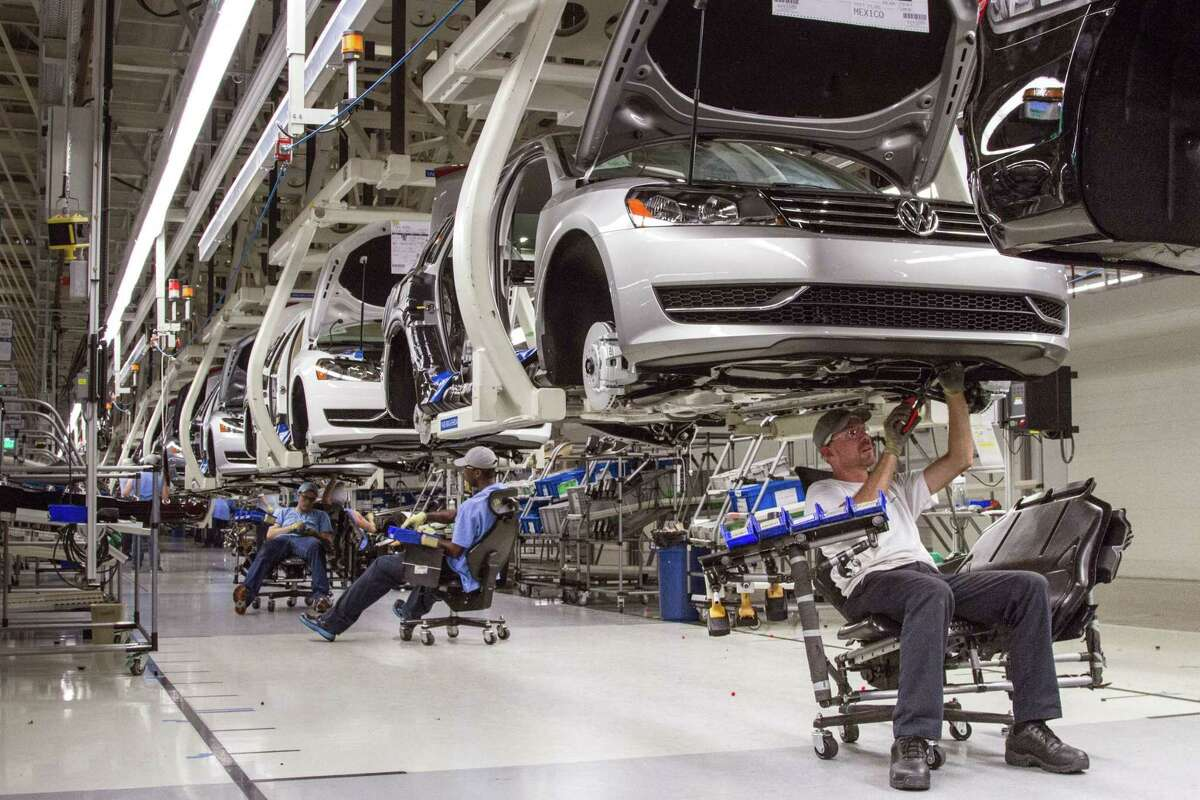 In this July 12, 2013 photo, employees at the Volkswagen plant in Chattanooga, Tenn., work on the assembly of a Passat sedan.