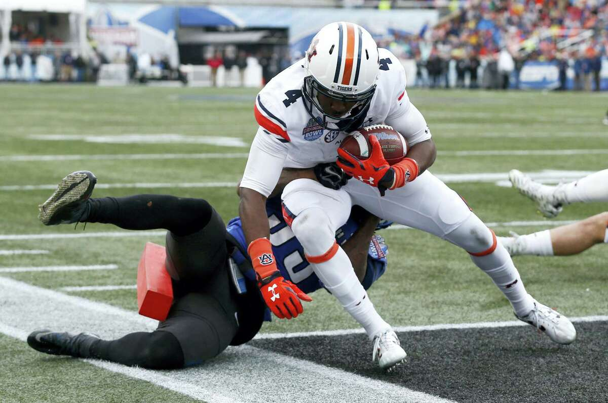 Auburn receiver Jason Smith (4) carries the ball in for a touchdown against Memphis defensive back Reggis Ball during the second half of the Birmingham Bowl on Wednesday in Birmingham, Ala.