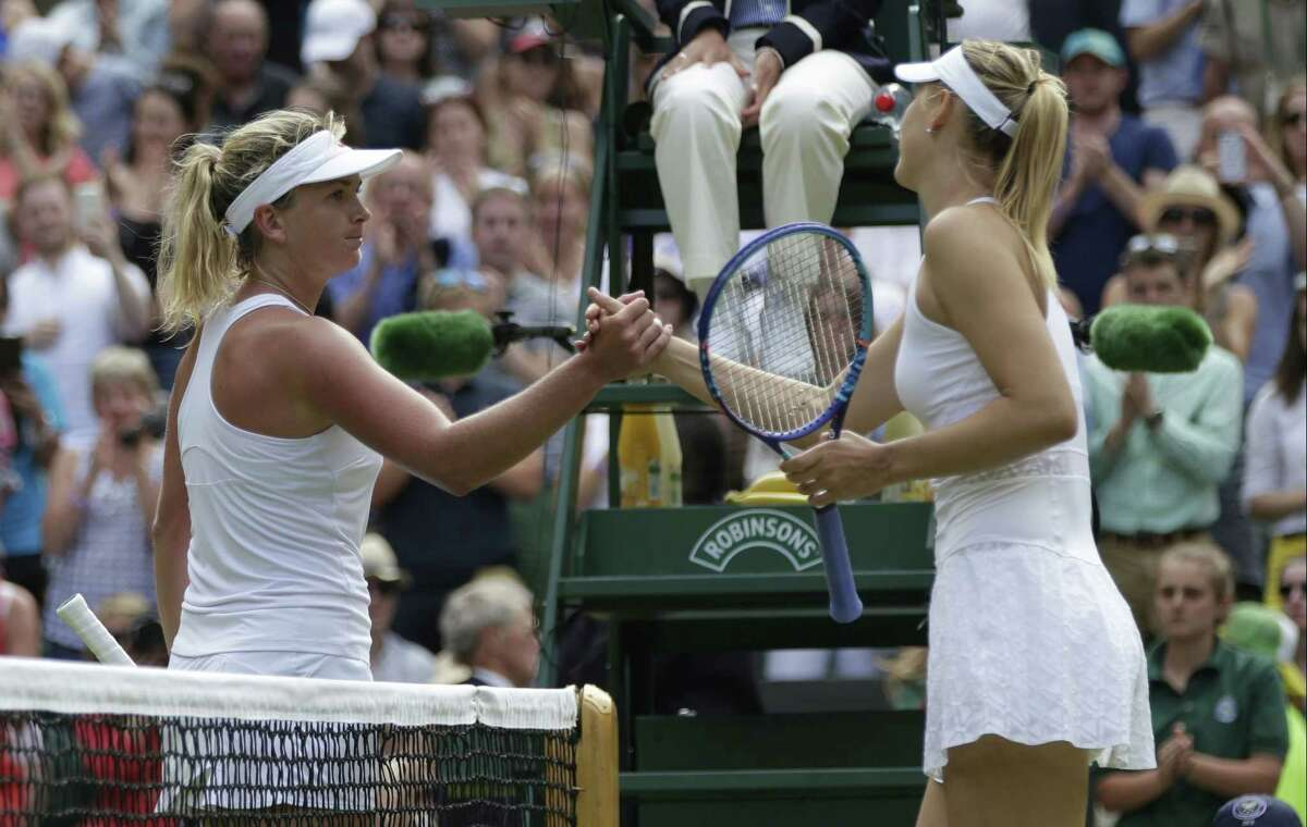 Maria Sharapova, right, shakes hands at the net with Coco Vandeweghe after winning their singles match at the All England Lawn Tennis Championships on Tuesday in Wimbledon, London.
