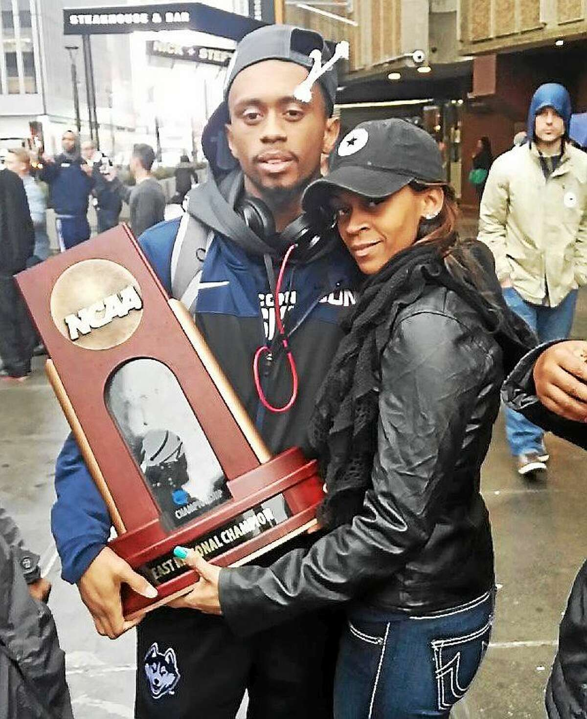 UConn senior Ryan Boatright and his mother, Tanesha, pose with the Huskies' national championship trophy.