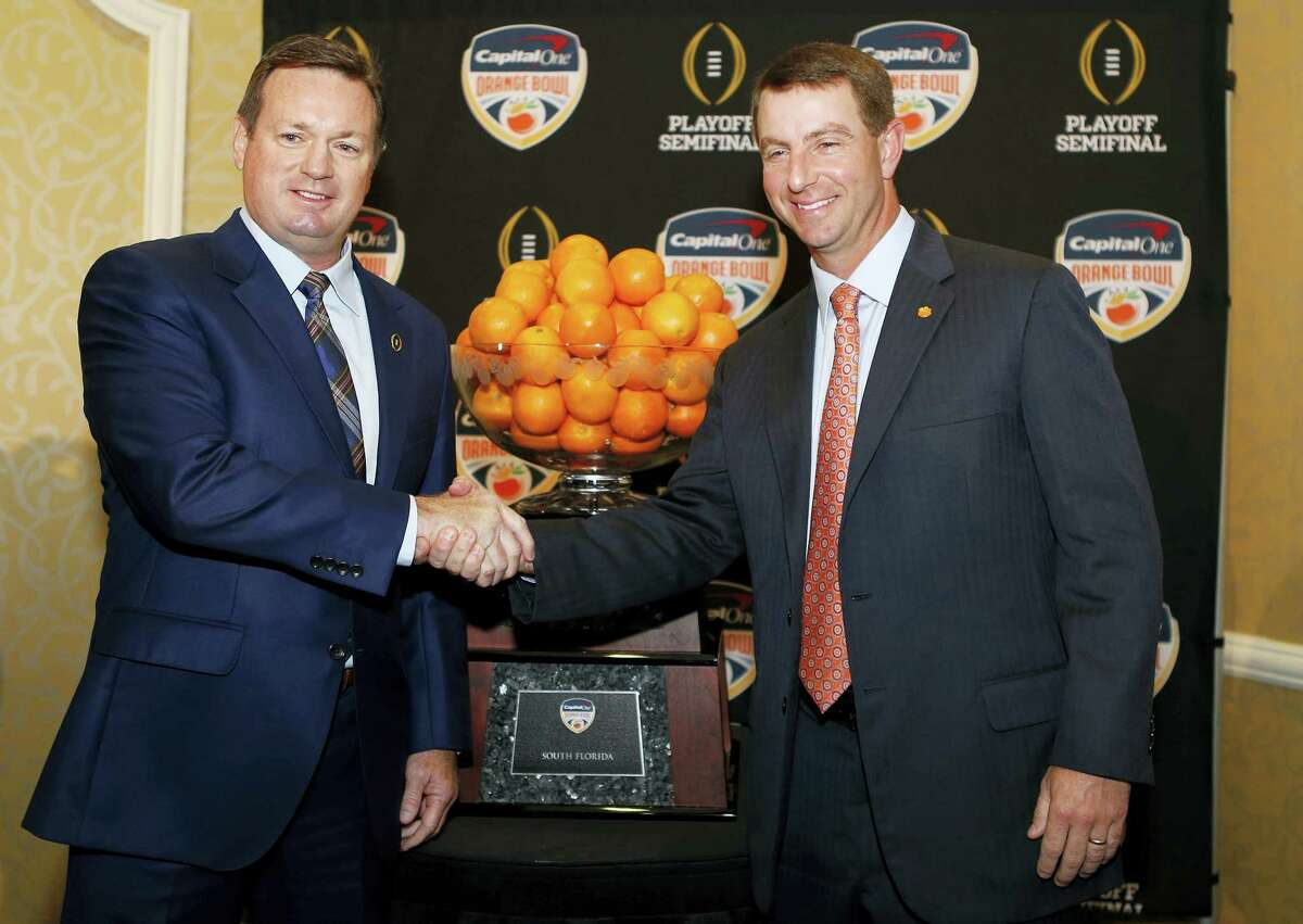 Oklahoma head coach Bob Stoops, left, and Clemson head coach Dabo Swinney shake hands in front of the Orange Bowl trophy Wednesday in Fort Lauderdale, Fla.