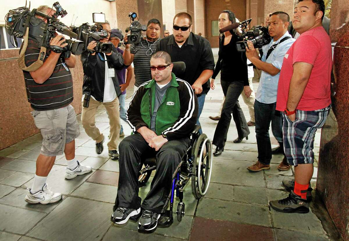 FILE - This June 25, 2014 file photo shows a wheelchair bound Bryan Stow surrounded by family and media as he is led into the Los Angeles County Superior Courthouse in Los Angeles.