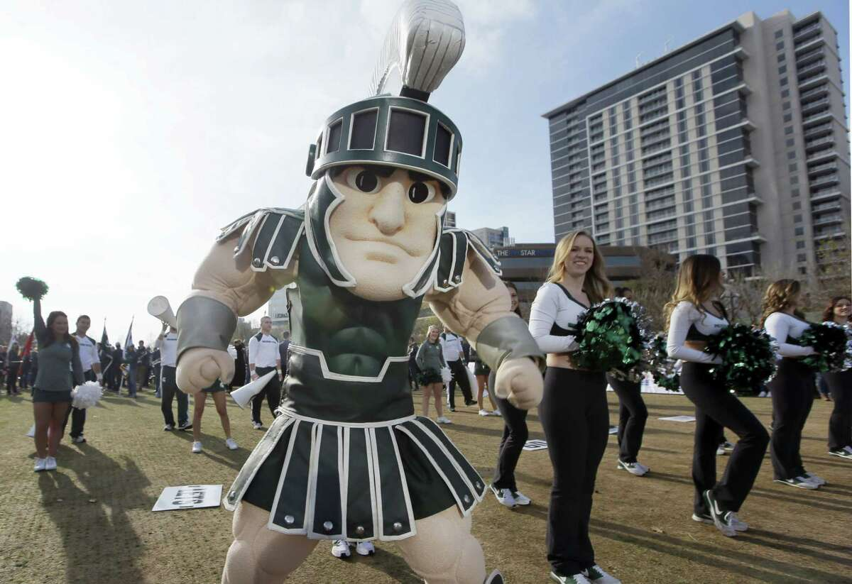 Michigan State mascot Sparty stands with cheerleaders during a rally for the Cotton Bowl in downtown Dallas on Wednesday.