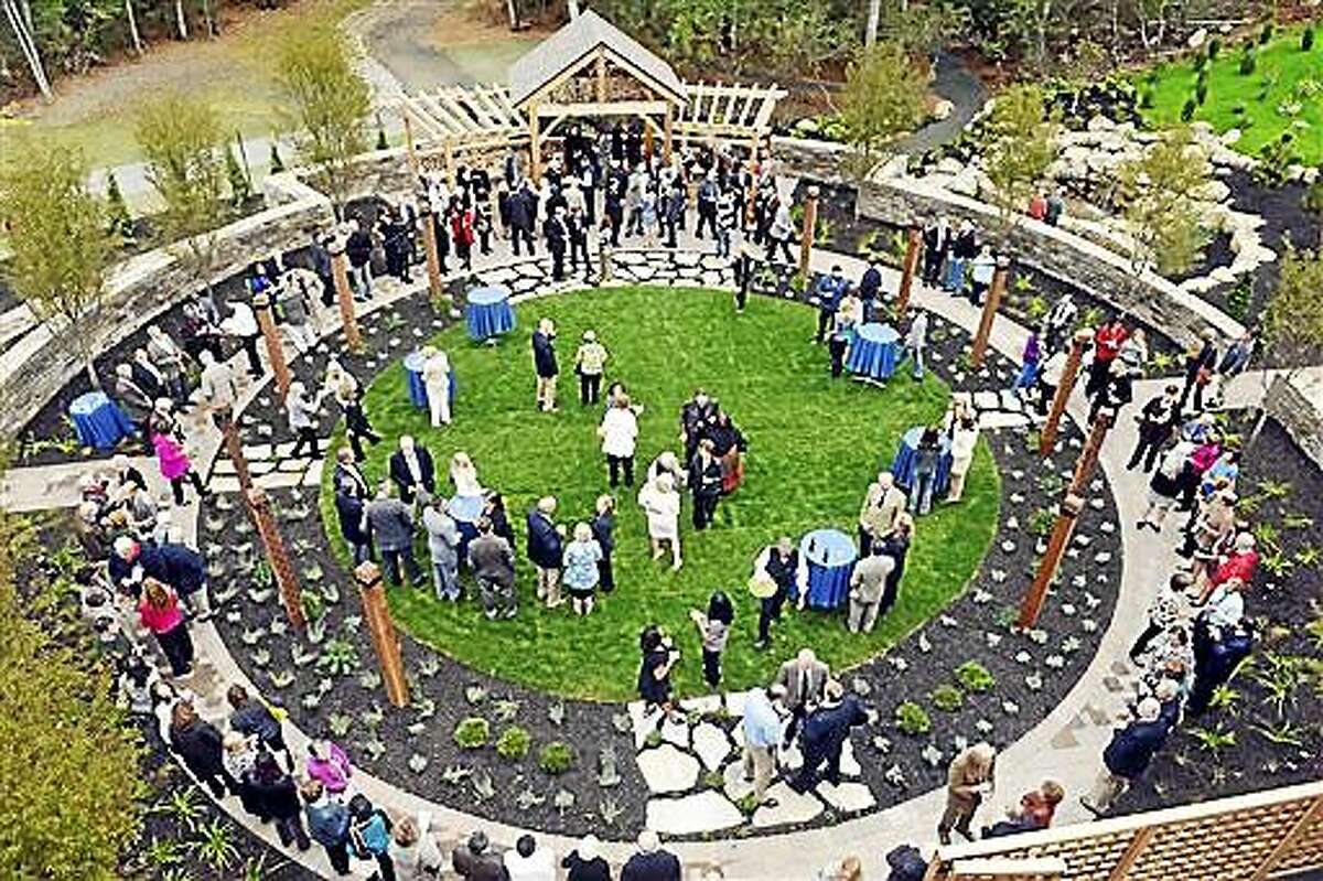 ADVANCE FOR SATURDAY, NOV. 1, 2014 AND THEREAFTER -- In this Thursday, Oct. 2, 2014 photo guests attend a dedication and ribbon-cutting ceremony in the Healing Garden, at the Lawrence + Memorial Cancer Center, in Waterford, Conn. The garden was designed for patients, families, and employees seeking a peaceful setting. (AP Photo/Tim Martin, The Day) MANDATORY CREDIT