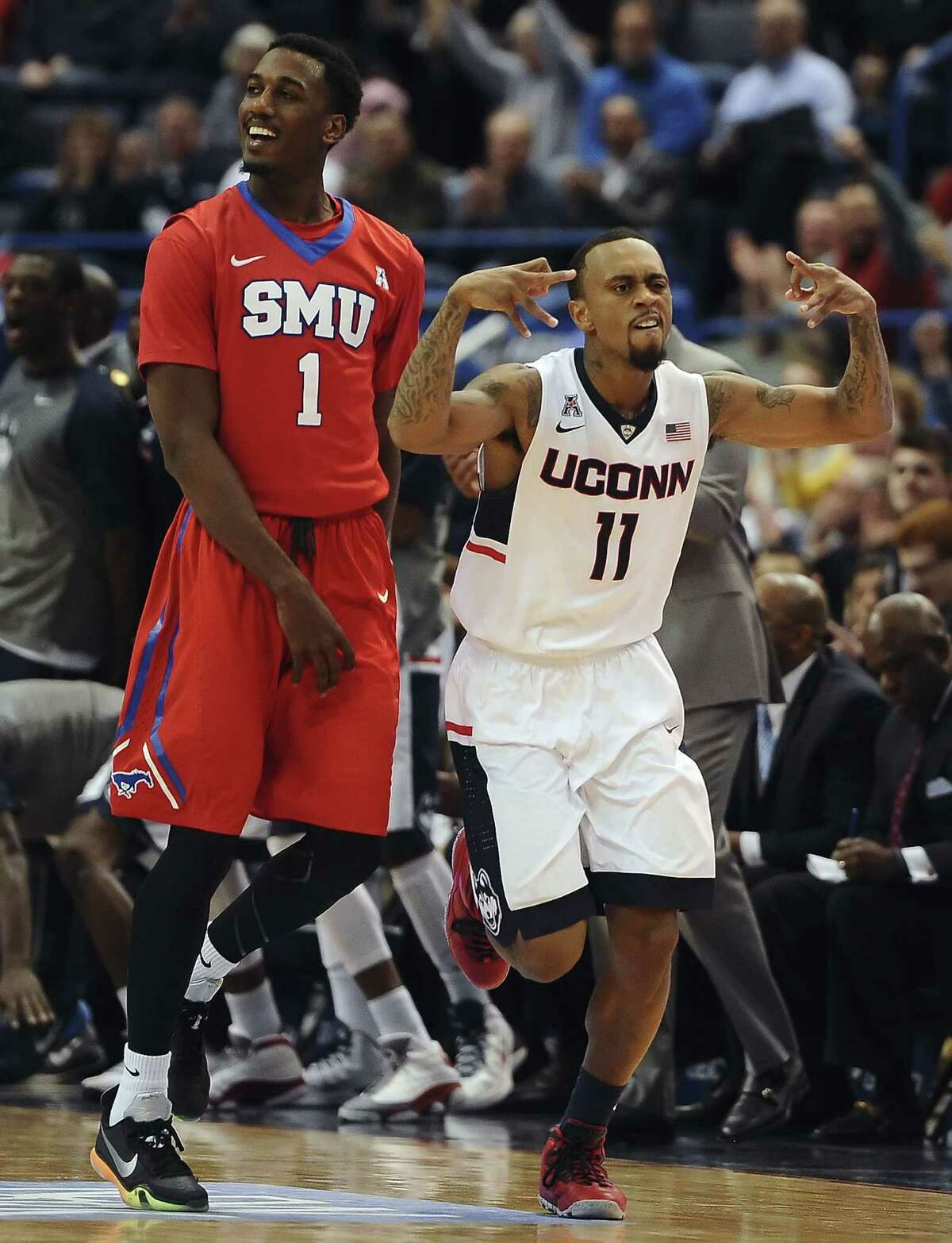 Connecticut's Ryan Boatright, right, reacts to hitting a three-point basket as he runs by SMU's Ryan Manuel, left, during the second half of an NCAA college basketball game, Sunday,March 1, 2015, in Hartford, Conn. UConn won 81-73. (AP Photo/Jessica Hill)