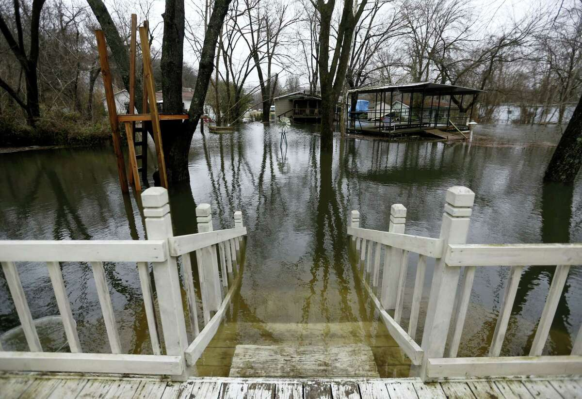 Floodwaters approach the deck of a home in Branson, Mo., caught in the rising waters of Lake Taneycomo on Monday.