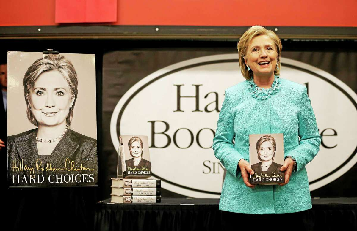 """Former Secretary of State HiIlary Rodham Clinton holds a copy of her new book """"Hard Choices,"""" at the start of a book signing at Harvard Book Store, Monday, June 16, 2014, in Cambridge, Mass."""