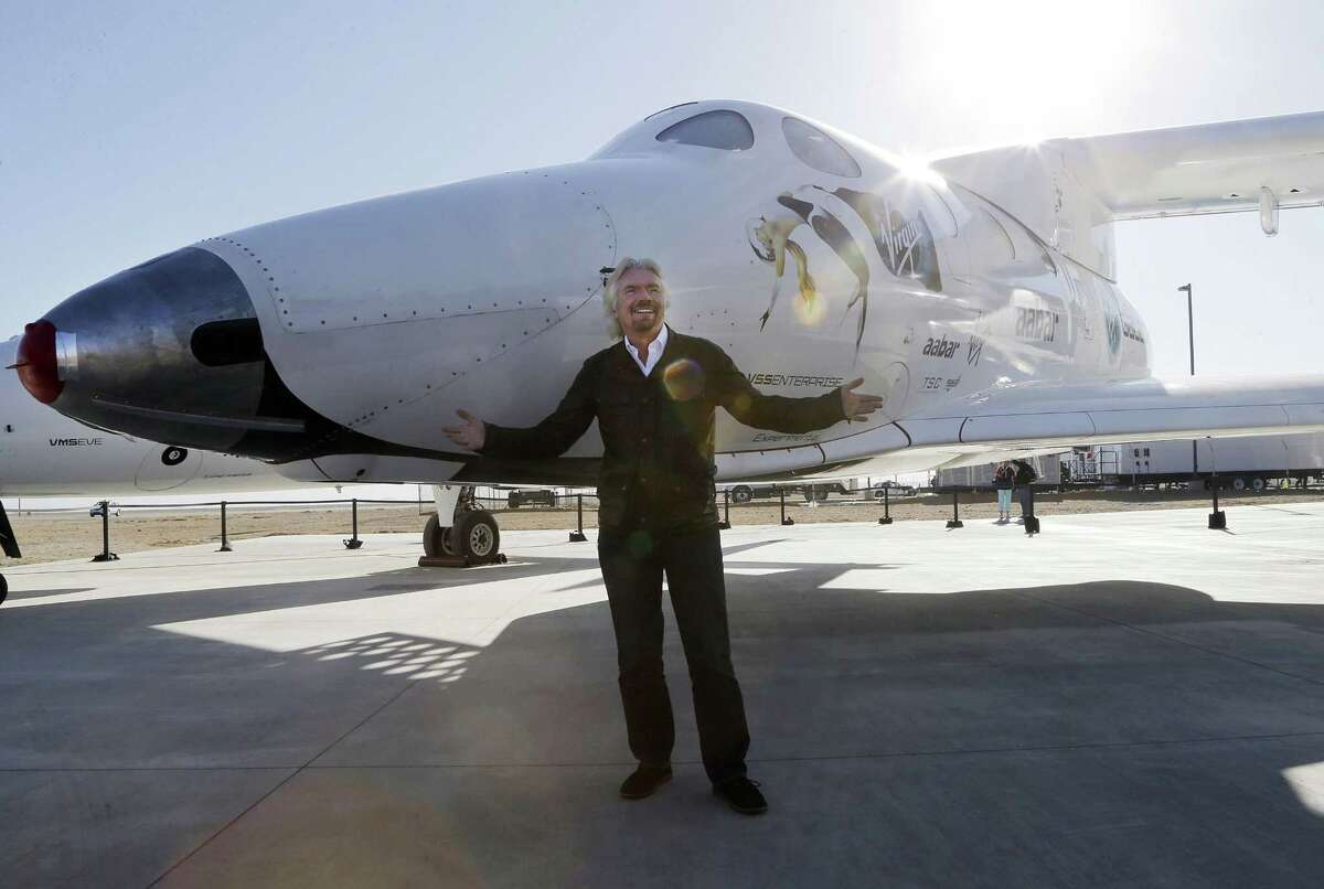 """FILE - In this Sept. 25, 2013, file photo, British entrepreneur Richard Branson poses with SpaceShipTwo at a Virgin Galactic hangar at Mojave Air and Space Port in Mojave, Calif. The Virgin Galactic's SpaceShipTwo space tourism rocket exploded Friday, Oct. 31, 2014, during a test flight, killing a pilot aboard and seriously injuring another while scattering wreckage in Southern California's Mojave Desert, witnesses and officials said. Virgin Galactic would not say what happened other than that it was working with authorities to determine the cause of the """"accident."""" (AP Photo/Reed Saxon, File)"""