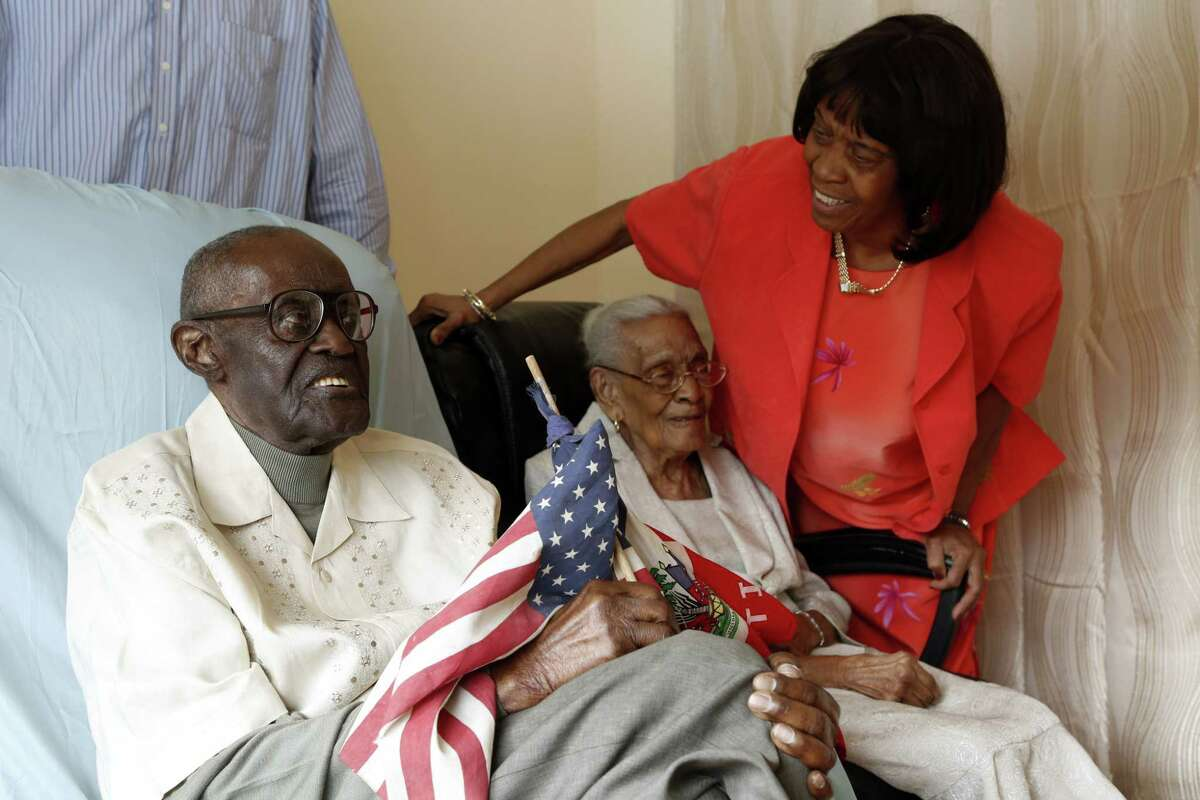 In this photo taken on Thursday, Feb. 26, 2015, Marie Yoland Eveillard speaks with her father Duranord Veillard and mother Jeanne, in Spring Valley. Duranord Veillard celebrates his 108th birthday on Saturday, Feb. 28, 2015 and his wife, Jeanne will turn 105 in May. The Veillards have been married 82 years and are one of the oldest married couples in New York.